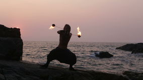 l-homme-tourne-le-feu-poi-se-tenant-sur-une-falaise-prs-de-l-ocan-au-coucher-du-soleil-45442943.jpg